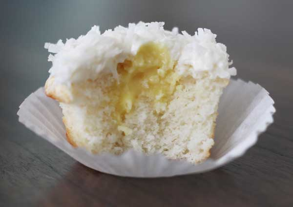 Coconut cupcakes - filled with coconut filling - topped with coconut cream cheese frosting. If you love coconut cake - these cupcakes are the ultimate!